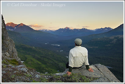 A backpacker watching the sunset over the Bremner River Valley in the Chugach Mountains, Wrangell St. Elias National Park, Alaska.