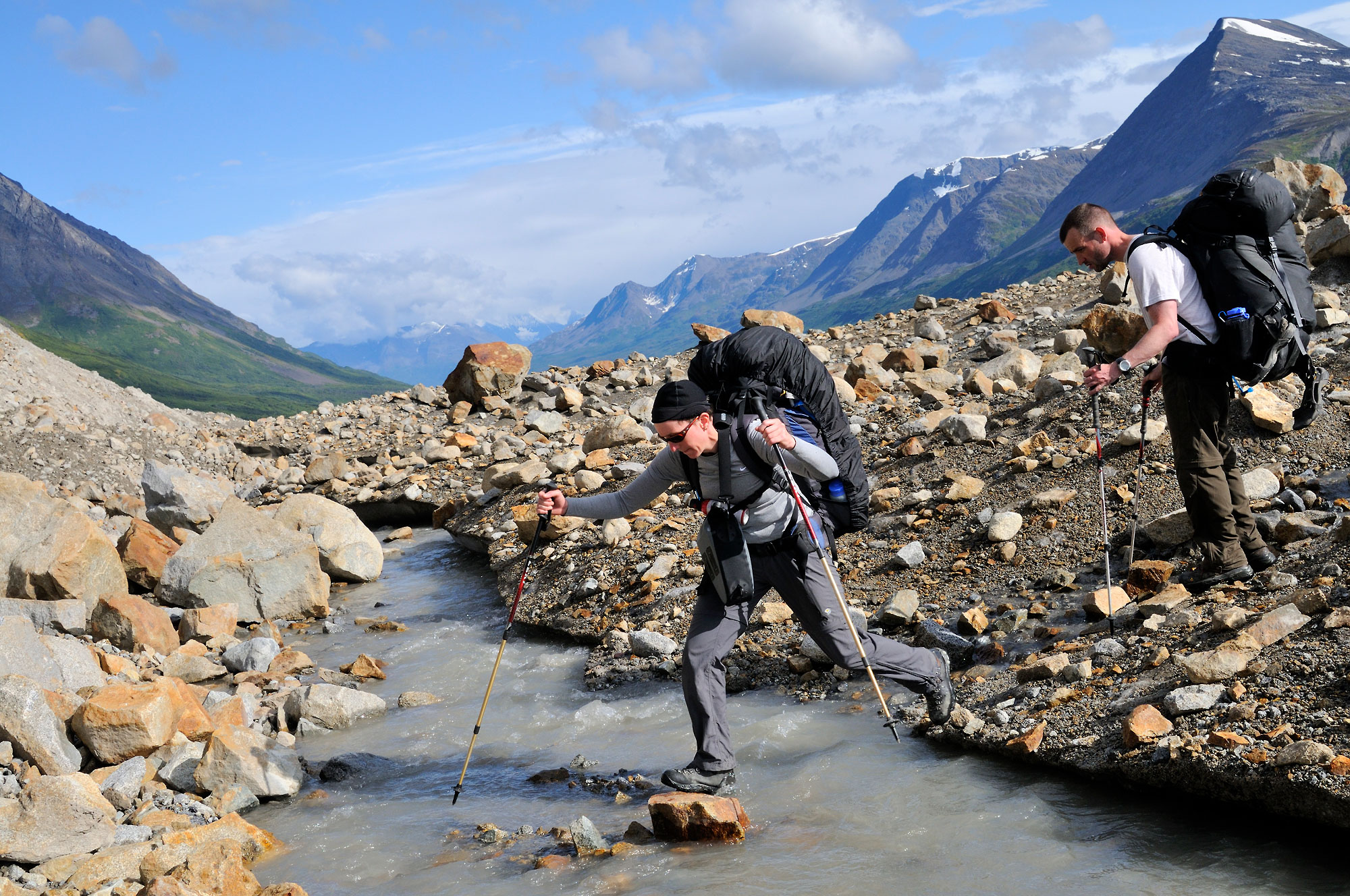 Backpackers crossing a stream on a glacier.