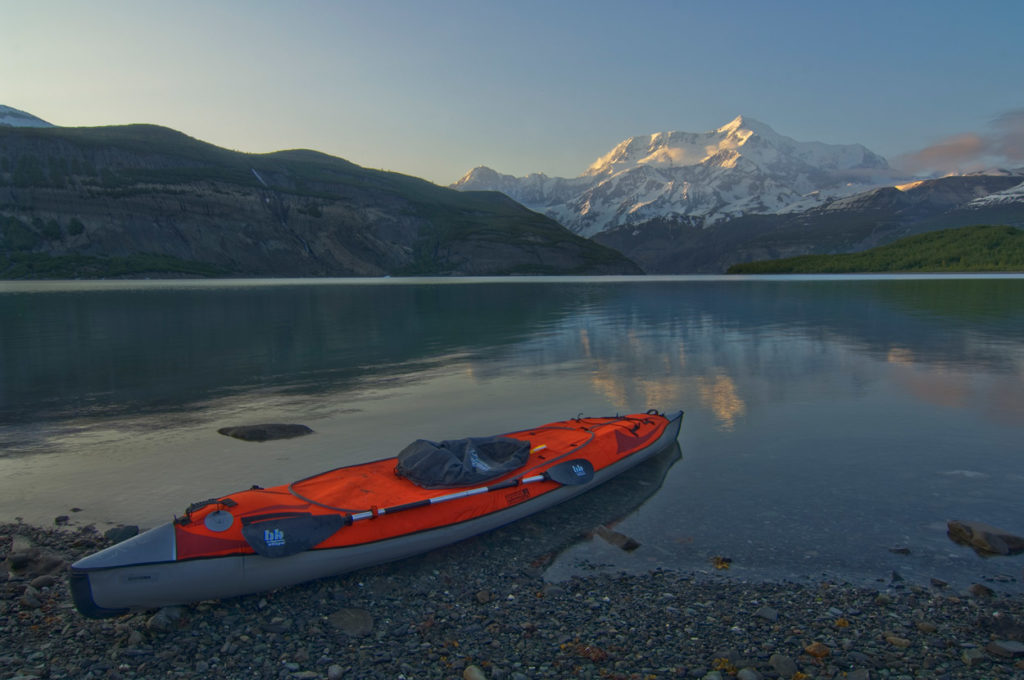Guided Alaska Sea kayak trip parked on shore with Mt. St. Elias, Icy Bay, Wrangell - St. Elias National Park, Alaska.