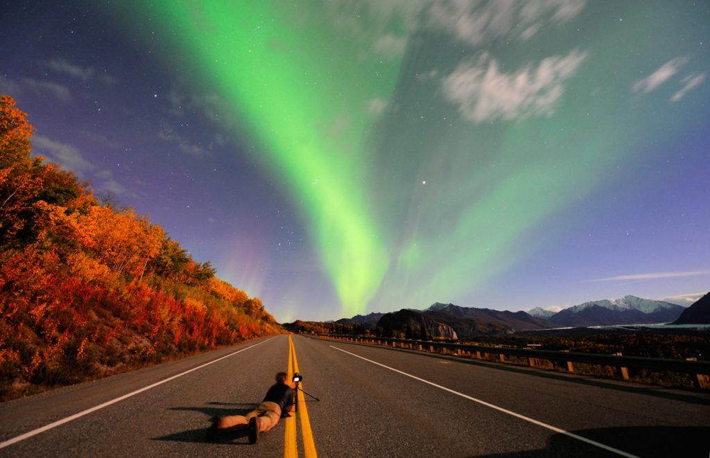 Northern lights photographer lying on Glenn Highway, Alaska photo tours.