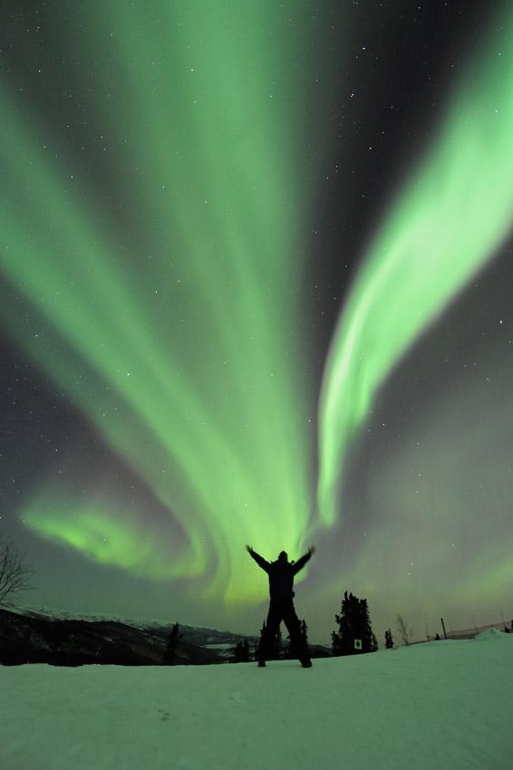 Aurora borealis and a photographer on aurora photo tour in Alaska.