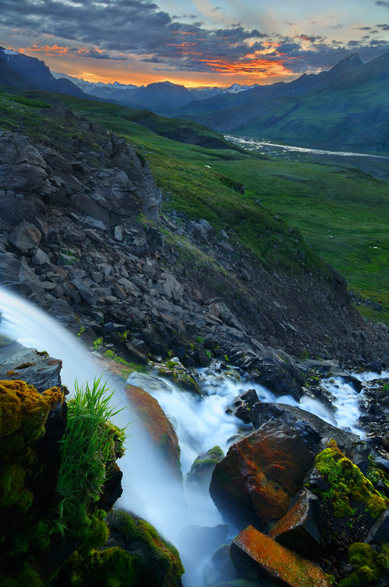Photo of a waterfall and sunset over Skolai Pass in Wrangell - St. Elias National Park, Alaska.